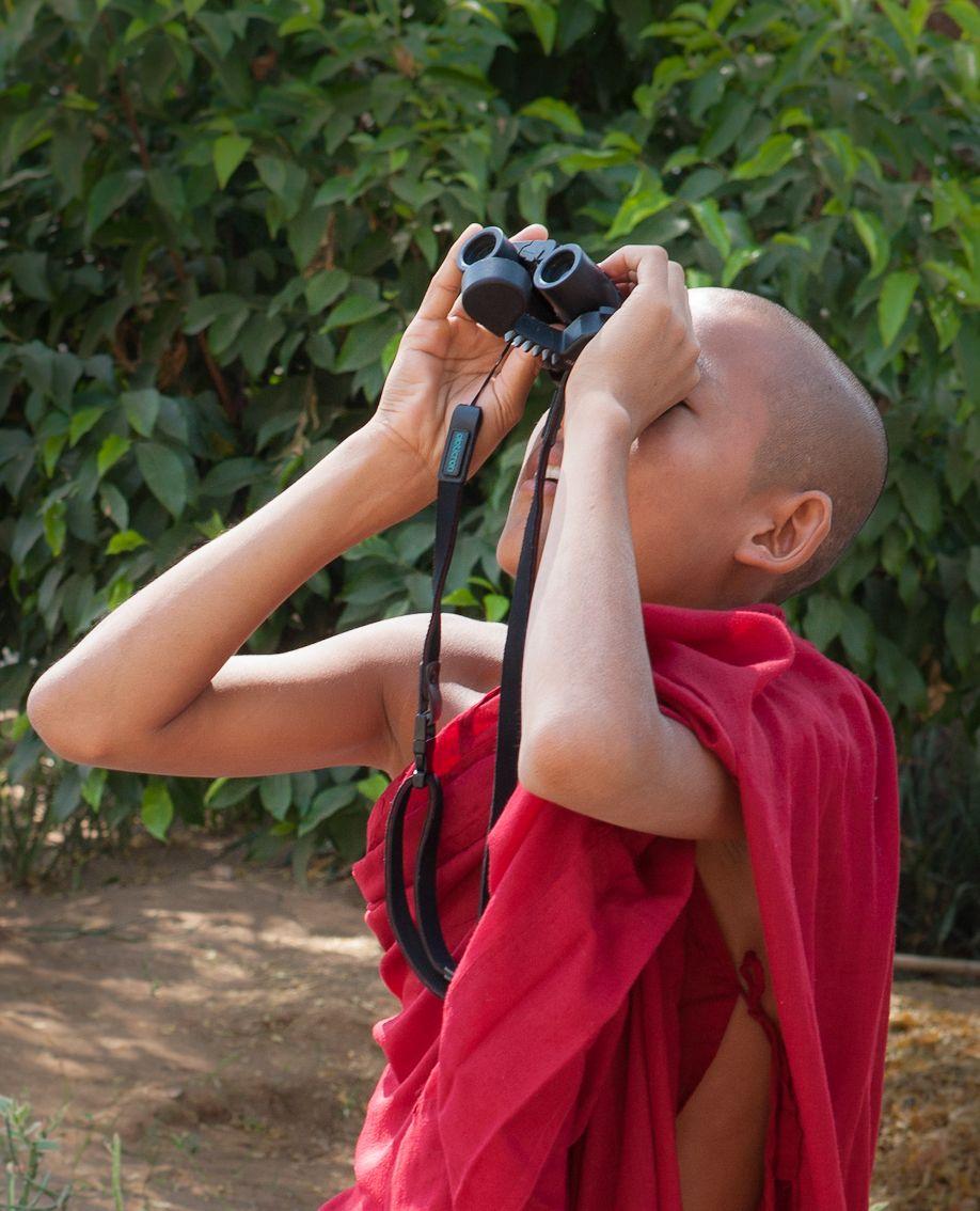 Myanmar Burma monk looking through binoculars at temple in Bagan