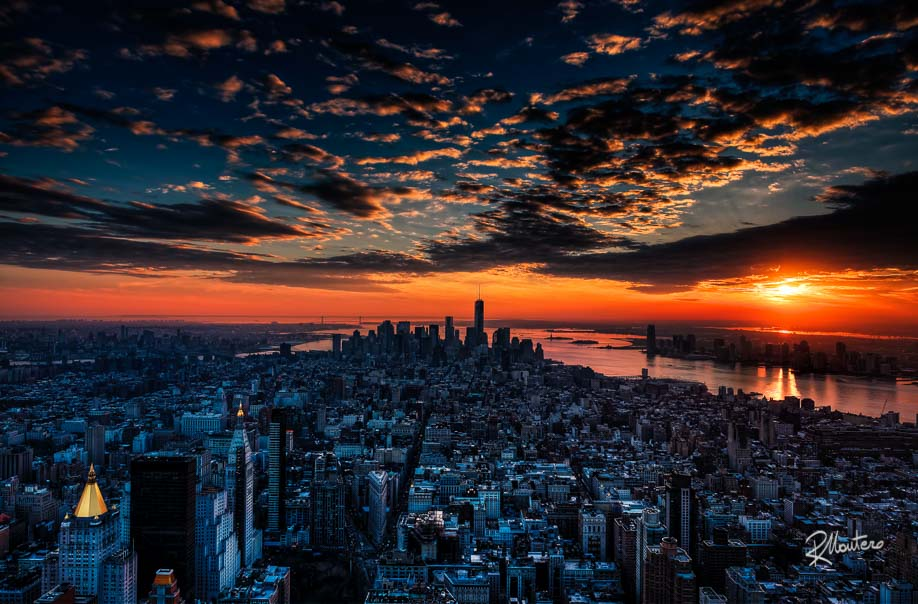 From the top of the Empire State Building, challenging the usual pressing crowd and the wind chill; while waiting for the night to frame the NY lights, the sky took fire with this stunning sunset. This is another shoot for which I travelled to NY. Got it! As usual I've tried to obtain an high level of detail, it is possible to see the most famous bridges, like the Brooklin Bridge and the Verrazzano Bridge then Ellis Island and Liberty Island with the silhouette of Lady Liberty against the red reflection in the water. The golden domes were reflecting the last rays of light and the first artificial lamps like mirrors interrupting the monotone colors of the buildings. I had to export in Adobe RGB to preserve the red gradient however as usual the original image (36,5 Megapixels) has more and more hues and better colors and if printed in large format can reach a maniacal level of detail.