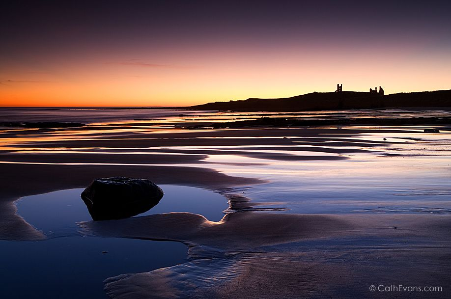View across Embleton Bay to Dunstanburgh Castle at dawn